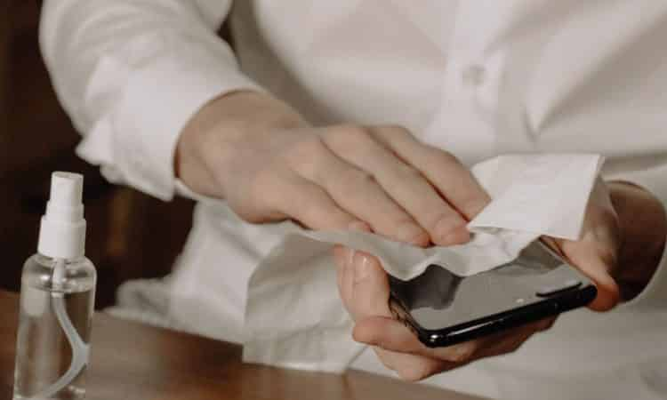 Sprit på telefon torkar med servett
