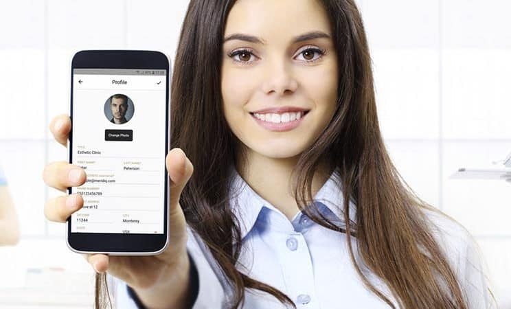 woman holding phone with MERIDIQ start screen